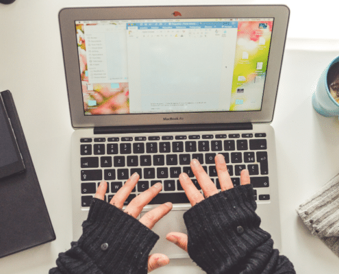 Woman in fingerless gloves typing
